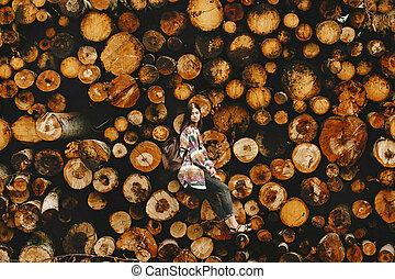 時髦, 行家, 婦女有背包, 坐, 在, 堆, ......的, 柴, 之外, the, 環境, 以及, 森林, 概念, 大气, 片刻, 人類, 規模