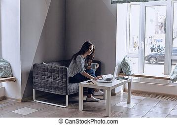 最好, 早晨, 開始, 由于, coffee., 美麗, 年輕婦女, 使用便攜式計算机, 以及, 看, 它, 當時, 坐在沙發上