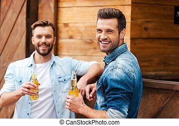 朗らかである, カウンター, バー, びん, 男性, 2, 若い見ること, ビール, 間, カメラ, 保有物, 傾倒, 古い, meeting., 友人