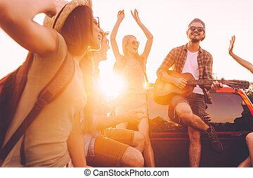 朗らかである, ever., グループ, ダンス, 人々, 積み込み, 若い, 一緒に, 旅行, ギター, ∥(彼・それ)ら∥, 間, トラック, 道, 楽しむ, 遊び, 最も良く