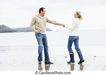 歩くこと, カップルの保有物手, 微笑, 浜
