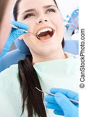 歯科医, 検査する, ∥, 口頭の虫歯, の, a, 若い患者