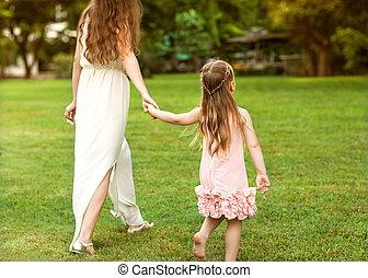母親和女兒, 走在公園, 扣留手, 在愛過程中