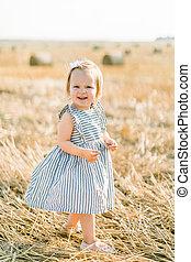 流行, かわいい 女, しまのある, 干し草山, フィールド, ポーズを取る, ∥あるいは∥, よちよち歩きの子, 立つ, 赤ん坊, 微笑, わずかしか, 服, 夏, 日当たりが良い, 小麦, 背景, カメラ, ベール
