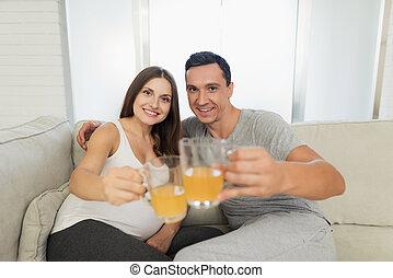 男の女性, 保有物, モデル, ライト, 妊娠した, sofa., ガラス, 次に, ジュース, 彼ら, カップ, うそ, 彼女。