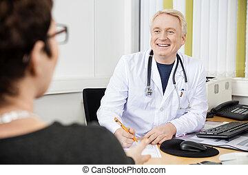 男性的醫生, 看, 女性, 病人, 在書桌