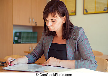 相當, 年輕, 老師, 是, 坐, 由于, 書, 在, 教室
