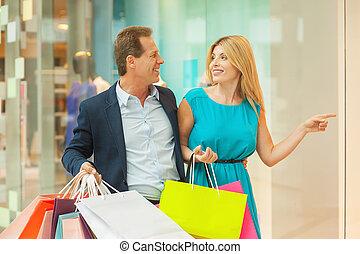 美しい女性, 買い物, 見なさい, 指すこと, これ, 恋人, dress!, 一緒に, 間, 成長した, 微笑, 離れて