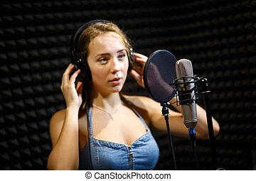 美しい, 女性, 実行者, 身に着けているヘッドホーン, 歌う歌, 中に, 録音, studio.