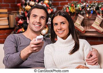 美しい, 監視 tv, 恋人, 木, 若い, 一緒に, 間, 結び付き, 他, 一緒に。, 背景, それぞれ, 微笑, 楽しむ, ショー, クリスマス, 情事