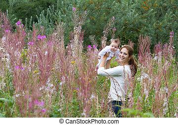 美しい, 若い, 母, ∥で∥, a, 女の赤ん坊, 中に, ピンクの花, フィールド