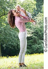 美麗的婦女, 拿住嬰孩, 在公園