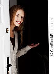 美麗的婦女, 是, 打開門, 以及, 邀請, 到, 來, 在。