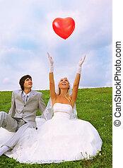 美麗, 穿, 新郎, 心形, 坐, balloon, grass;, 天空, 年輕, 新娘, 綠色白色, 衣服, 投擲,...