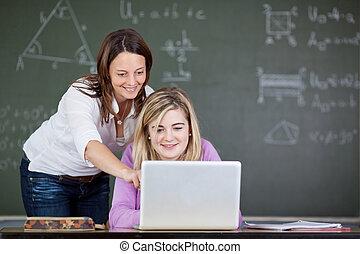 老師, 協助, 學生, 在, 使用便攜式計算机, 在書桌