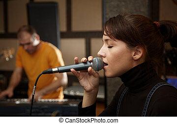 聲樂家, 女孩, 是, 唱, 在, studio., 鍵盤表演者, 在, 模糊不清