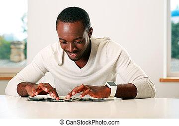 肖像画, の, a, 幸せ, アフリカの男, テーブルの着席, ∥で∥, ビルズ, の, 我々ドル