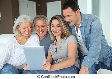 肖像, ......的, 高興的家庭, 坐, 在, 沙發, 由于, 電子, 片劑