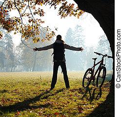 興奮, 婦女, 騎車者, 站立, 在, a, 公園, 由于, 手伸展, 擁抱, 生命力, freedom., 戶外