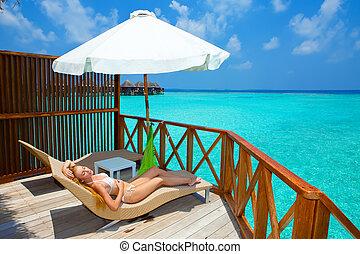 若い女性, 上に, chaise の ラウンジ, 下に, パラソル, 近くに, ∥, sea., maldives.