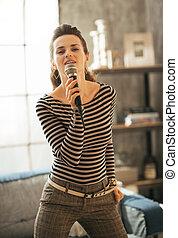 若い女性, 歌うこと, ∥で∥, マイクロフォン, 中に, 中二階の アパート
