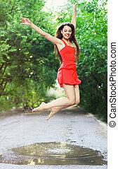 若い, 幸せな女性, 身に着けていること, 赤いドレス, 跳躍, に, a, 水たまり