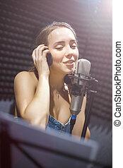 若い, 白, 女の子, 身に着けていること, ヘッドホン, そして, 歌うこと, に, マイクロフォン, 中に, レコーディングスタジオ