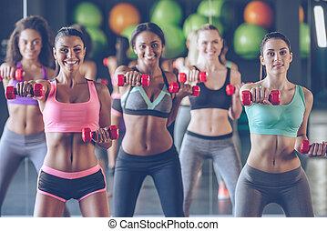 變得健康, 由于, smile., 年輕, 美麗的婦女, 在, 運動裝, 由于, 完美, 身体, 行使, 由于, dumbbells, 以及, 看  照相機, 由于, 微笑, 在, 體操