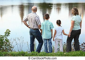 跟二個孩子一起的家庭, 在, 早, 秋天, 公園, 近, pond., 他們是, 看, water.