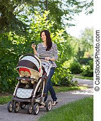 跟嬰孩一起的女人, 車, 使用, 移動電話, 在公園