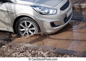 運転, つぼ穴, 自動車, water., 大きい, thtough, 危ない, roadbed., 満たされた, ...