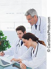 隊, ......的, 醫生, 一起工作, 以及, 觀看, 某事, 上, 他們, 膝上型, 在, 醫學的辦公室