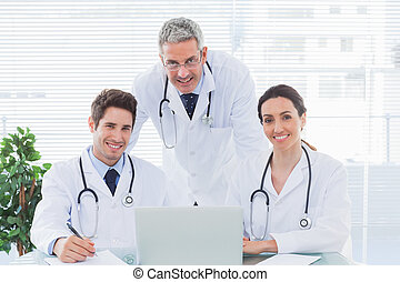 隊, ......的, 醫生, 一起工作, 由于, 他們, 膝上型, 看  照相機, 在, 醫學的辦公室