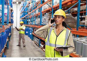 電話, モビール, 女性, 話し, 保有物のクリップボード, 労働者, 倉庫