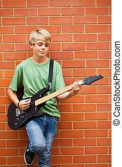 青少年男孩子, 演奏吉他, 在戶外