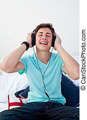 青少年, 听, 到, the, 音樂, 在, 他的, 寢室, 由于, 頭戴收話器