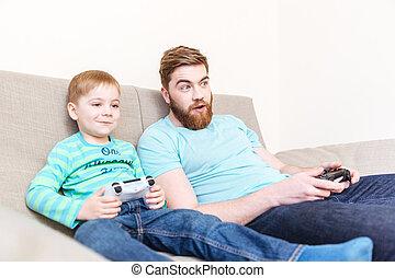 驚かせられた, 父, プレーのコンピュータゲーム, ∥で∥, 彼の, 息子, 上に, ソファー