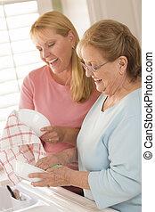 高级成年人, 妇女, 同时,, 年轻女儿, 谈话, 在中, 厨房