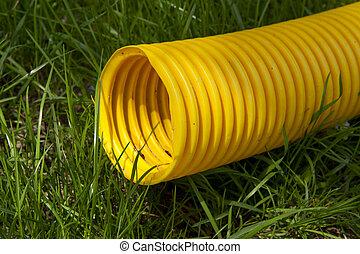 黄色, プラスチック管, 上に, 緑の草