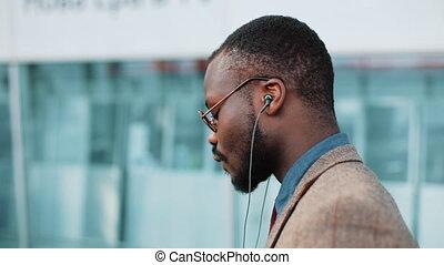 건물, 동안, 광고하는 것, 사무실, african, 쉬다, 미국 영어, 노동자, 은 무용한다, 음악, concept:, 은 걷는다, 실업가, 그, smartphone., 은 듣는다