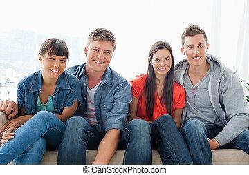 그룹, 보기, 착석, 소파, 동안, 카메라, 그들, 앞으로 기대는, 미소, 약간