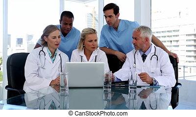그룹, 의, 의사, 을 사용하여, a, 휴대용 퍼스널 컴퓨터, 옷