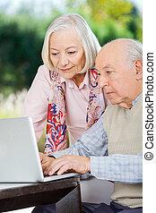 나이가 지긋한 커플, 휴대용 개인 컴퓨터를 사용하는 것