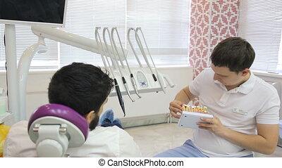 나이 적은 편의, 남성, 치과 의사, 을 사용하여, a, 이, 모델, 말한다, 환자, 은 이다, in 의자, 약, 길, 의, treatment.