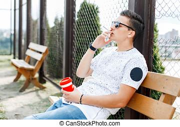 나이 적은 편의, 내리누르게 된다, 앉아 있고 있는 사람, 통하고 있는, a, 벤치, 와..., smokes., 사람, 보유, a, 커피잔, 에서, 그의 것, 건네라.