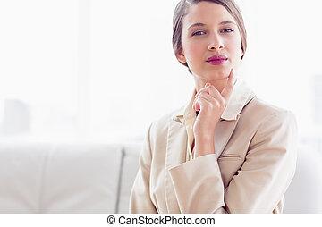 나이 적은 편의, 생각, 여자 실업가, 소파에 앉아 있는 것, 사진기를 보는