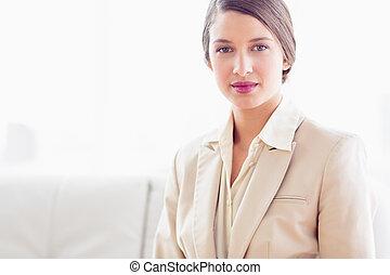 나이 적은 편의, 여자 실업가, 소파에 앉아 있는 것, 사진기를 보는