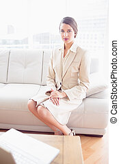 나이 적은 편의, 여자 실업가, 소파에 앉아 있는 것