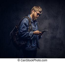 대담하게 맞서게 된다, 유행을 좇는 사람, 사람, 선글래스를 끼는 것, 와..., 배낭, 몸치장을 한다, 에서, jeans, 재킷, 을 사용하여, a, 정제, 컴퓨터, 통하고 있는, a, 암흑, 배경.