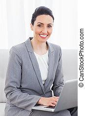 미소, 여자 실업가, 휴대용 개인 컴퓨터를 사용하는 것, 소파에 앉아 있는 것